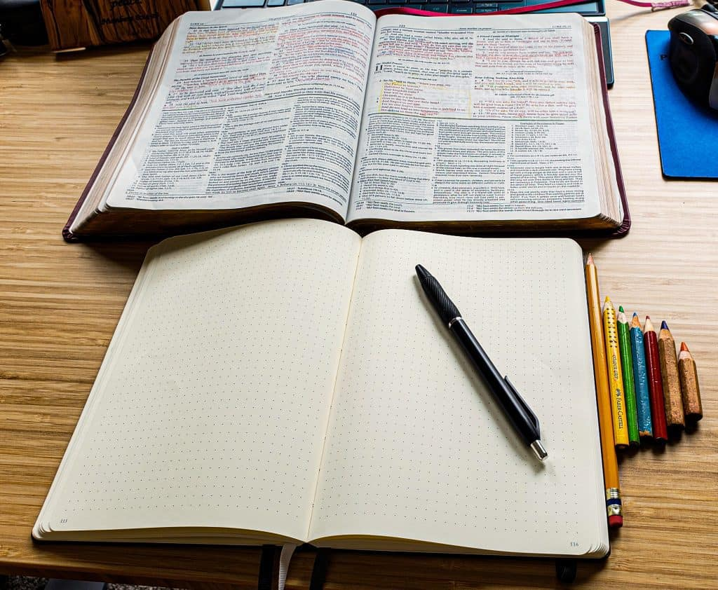An open Bible and an open empty journal below it. Next to the journal are several color pencils.