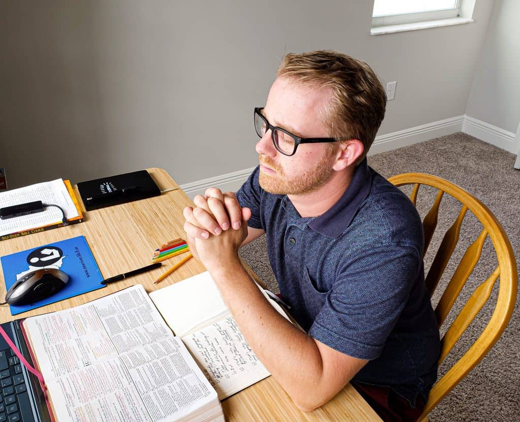 Blond man with glasses praying with folded hands sitting at an office desk with his Bible and journal opened