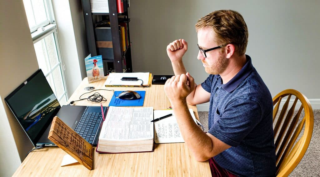 Man sitting at a desk. He rests his elbows on the desk with his fists going straight up in the air. In front of him is an open Bible, open journal, and a Laptop.