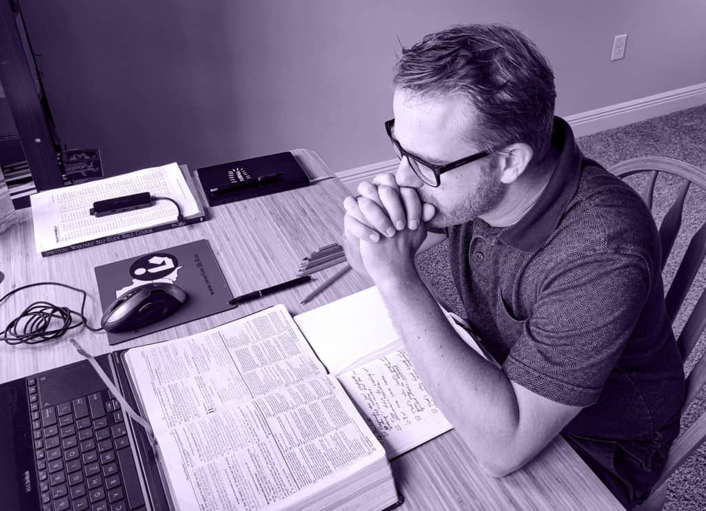 Man sitting at a desk resting his elbows on the desk. His hands are folded in front of his mouth in a prayer pose. in front of him are an open Bible and open Journal.