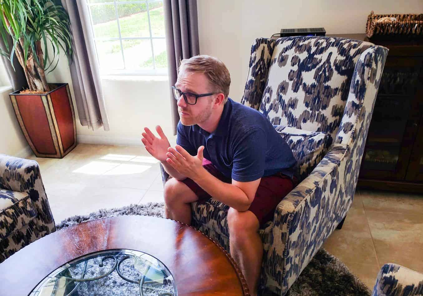 Blond man with glasses sitting in an armchair raising his hands with his elbows resting on his knees.
