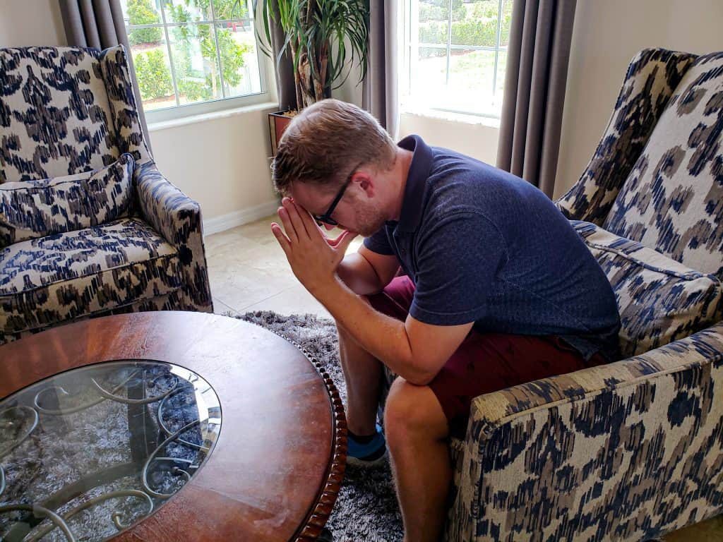 Man sitting at a round living room table in an armchair hunched over with praying hands touching his forehead.