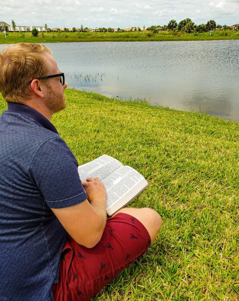 Blond man sitting in the grass holding an open Bible in his lap overlooking a pond.