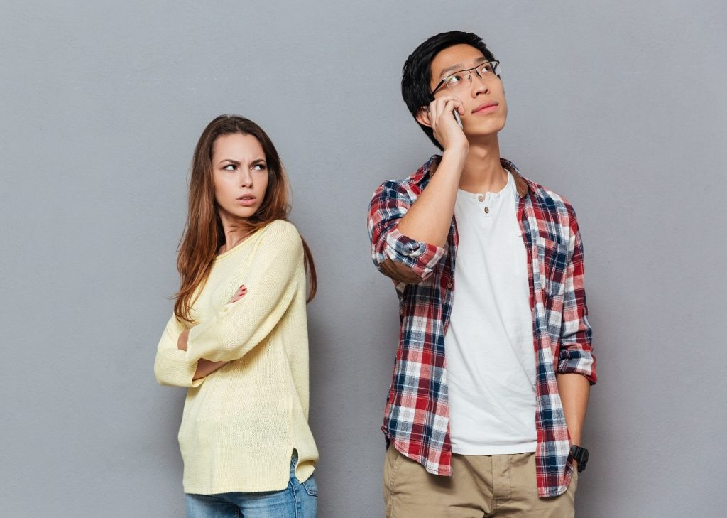 Portrait of upset angry girl watching her boyfriend talking on mobile phone isolated on the gray background